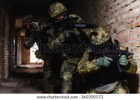 Team of three elite police marksmen in German uniform with weapon in building/Spec ops team during military operation