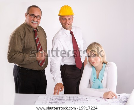 team of three engineers of different age at the meeting - stock photo