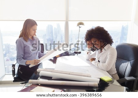 Team of two female architects, sitting at desk in office skyscraper. The women talk reviewing a building plan. Medium shot - stock photo