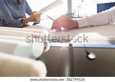 Team of two female architects, sitting at desk in office with building plans on desk. Cropped view of hand holding pencil.  - stock photo