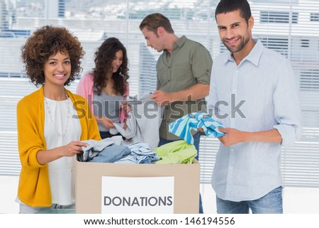 Team of volunteers taking out clothes from a donation box for a charity - stock photo