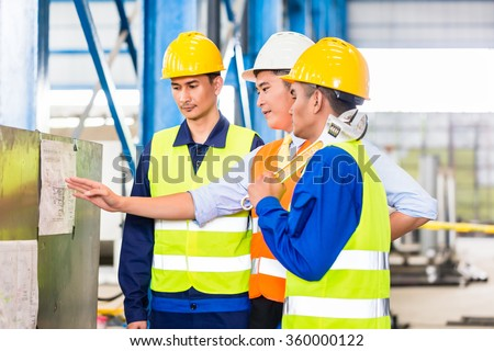 Team of workers and engineer  in Factory at production training with laptop - stock photo
