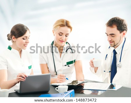 Team of young and smart medical workers over abstract hospital background - stock photo