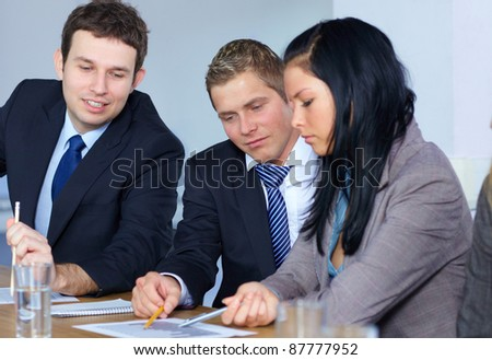 Team of 3 young business people work on some documents, all sitting at conference table - stock photo