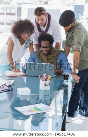Team of young creative designers working on laptop - stock photo