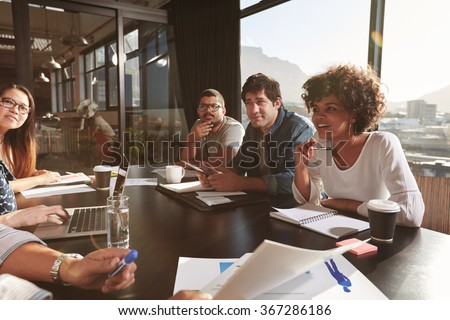 Team of young people discussing new business plan during a meeting in office. Mixed race team of designers discussing net projects in office. - stock photo
