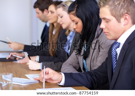 Team of 5 young people sitting at conference table and work on some paperwork, focus on female with black hair - stock photo