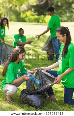Team of young volunteers picking up litter in the park - stock photo
