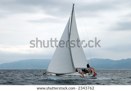 Team on a sailing cruise under clouds on Adriatic sea - stock photo