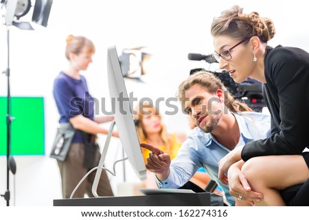 Team or Director discussing during a break the scene direction on set of a commercial video production or reportage at a screen - stock photo