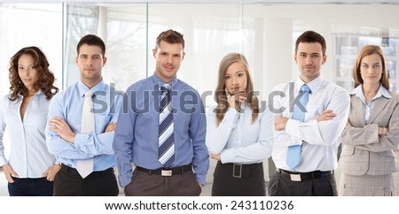 Team photo of successful young confident businesspeople standing at office. - stock photo