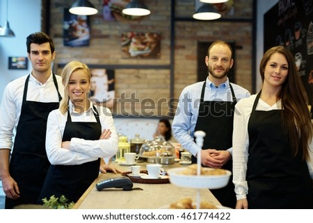 Team photo of waiters and waitresses standing in apron in cafeteria.