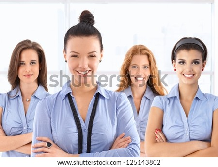 Team portrait of attractive young female front office workers in blue uniform, looking at camera, smiling.