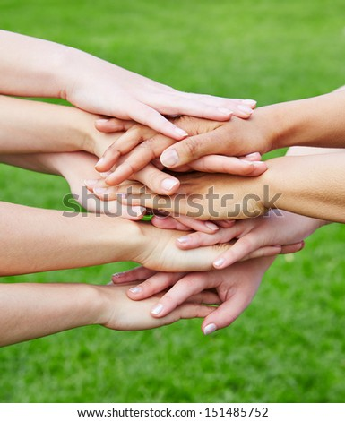 Team stacking many hands for motivation in green nature - stock photo
