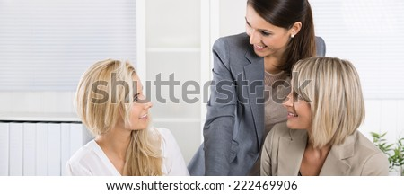 Team: Successful business team of woman in the office talking together. - stock photo