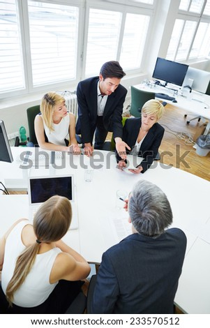 Team talking in business meeting at conference table about future projects - stock photo