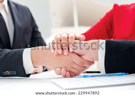 Team. Three successful and confident businesspeople shake hands. Businesspeople in formal attire sitting in an office at a desk and smiling at the camera - stock photo