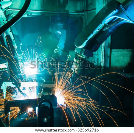 Team welding robots represent the movement in the automotive parts industry - stock photo