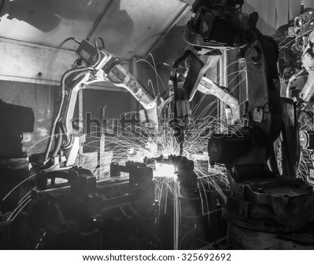 Team welding robots represent the movement in the automotive parts industry black white - stock photo