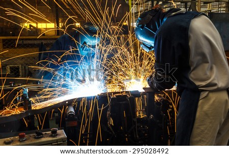 Team worker with protective mask welding. - stock photo