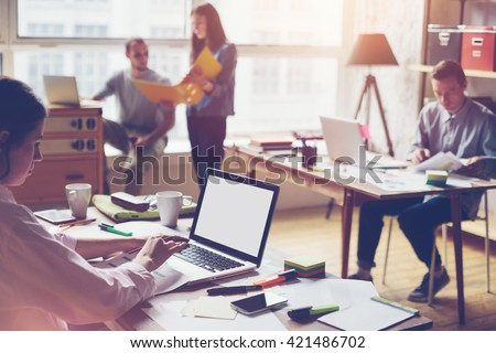 Team working in big loft office. Laptop typing and new project discussing. - stock photo