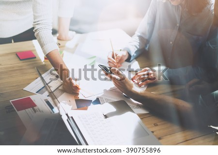 Team working. Photo young businessmans crew preparing  new startup project in modern loft. Generic design notebook on wood table. Horizontal, film effect, sunlights - stock photo