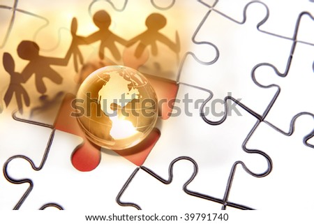 Team working together around globe on puzzle. - stock photo