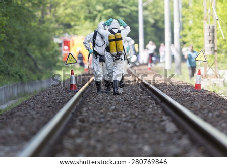 Team working with toxic acid and chemicals is approaching a chemical cargo train crash near Sofia. Teams from Fire department are participating in a training with spilled toxic and flammable materials - stock photo