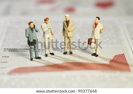 Teamwork And Analysis, four miniature businessmen standing analysing performance above a red bar graph. - stock photo