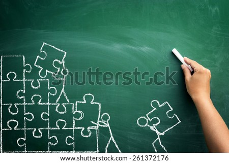 teamwork and puzzle pieces with person signs over blackboard, business team building concept - stock photo