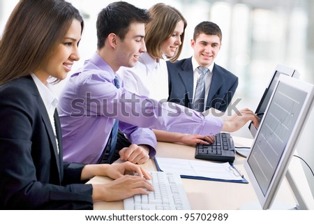 Teamwork - Business man showing something on computer screen to colleagues