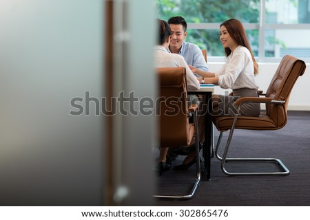 Teamwork: business people discussing project in the office - stock photo