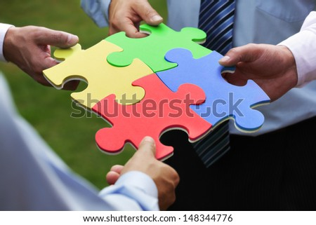 Teamwork concept four business people holding jigsaw puzzle pieces together - stock photo
