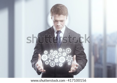 Teamwork concept with businessman holding abstract gear mechanism - stock photo