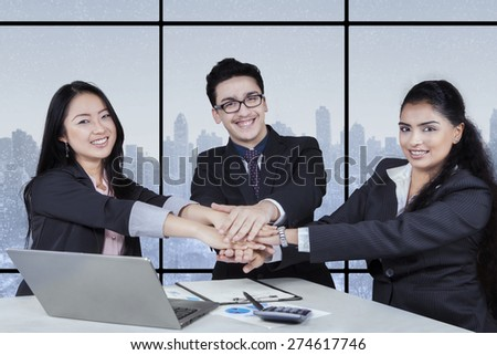 Teamwork concept with multi ethnic business team joining their hands together - stock photo