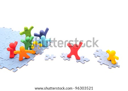 teamwork concept with plasticine people - colorful group is working together to save their little yellow fellow - isolated on white - stock photo