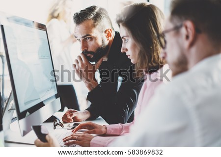 Teamwork concept.Young creative coworkers working with new startup project in modern office.Group of three people analyze data on desktop computer.Horizontal,blurred background