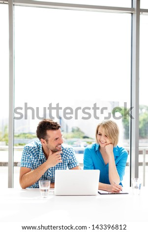 Teamwork concepts. Happy couple working together on laptop in the office. - stock photo