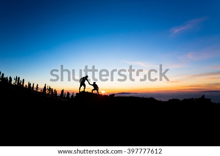 Teamwork couple helping hand trust help silhouette in mountains, sunset. Team climbers man and woman help each other in mountains.Beautiful inspirational sunset landscape on Tenerife Canary Islands. - stock photo