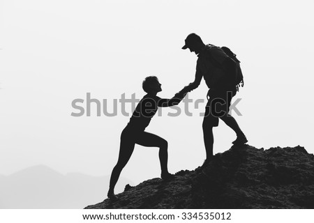 Teamwork couple helping hand, trust, help silhouette in mountains, sunset. Team of climbers man and woman hikers, help each other top of mountain, climbing together, beautiful inspirational landscape - stock photo