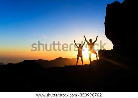 Teamwork couple hikers success in sunset mountains, accomplish with arms up outstretched. Young man and woman on rocky mountain range looking at beautiful inspirational landscape view, Gran Canaria. - stock photo