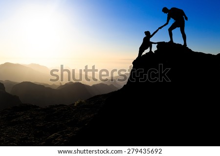 Teamwork couple hiking help each other trust assistance silhouette in mountains, sunset. Team of climbers man and woman hiker helping each other on top of mountain, climbing trust beautiful landscape. - stock photo