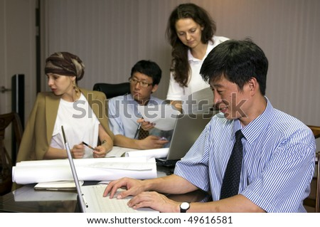 Teamwork: group of young business managers, working in office - stock photo