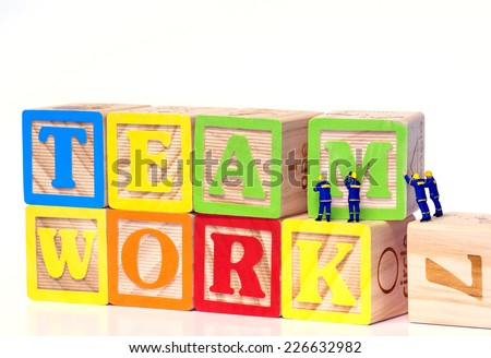 Teamwork - Miniature construction worker figurines posed as if building the word Teamwork with toy blocks.