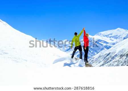 Teamwork motivation accomplish, couple hikers climbers with arms up, fitness and sport woman success in winter mountains. Inspiration beautiful landscape and healthy lifestyle on snow in Himalayas - stock photo