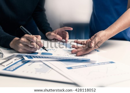 Teamwork of business women working with financial charts and report on workplace at the office. - stock photo