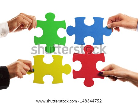 Teamwork strategy or partnership concept with business team holding jigsaw pieces together - stock photo