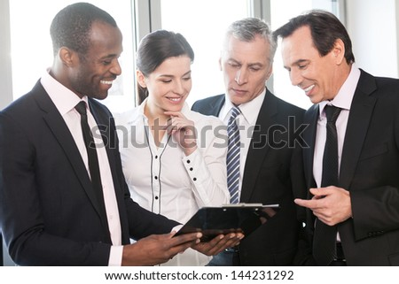 Teamwork talking. Four business people collaborate on work in a black tablet - stock photo
