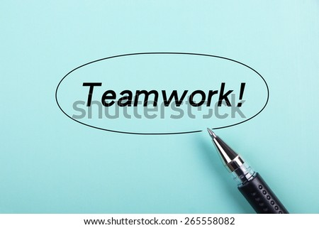 Teamwork text is on blue paper with black ball-point pen aside. - stock photo
