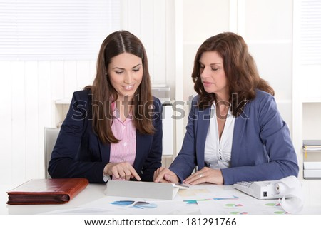 Teamwork: two business woman working together. - stock photo